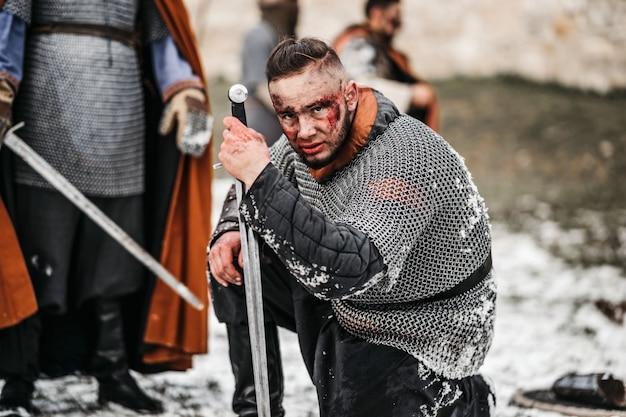 戦闘で死んだ兵士の前で、チェーンメールの鎧とマントルの中世の戦士がひざまずきます。