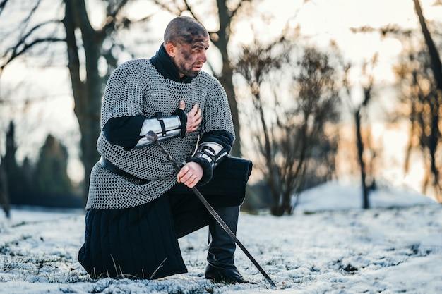 Средневековый воин в кольчужных доспехах на коленях с мечом в руке и грязным лицом после битвы. фон леса и снега