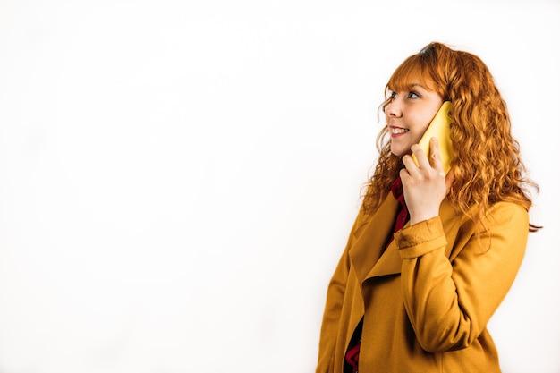 孤立した白い壁に黄色いコートを着て電話で話している幸せな赤毛の女性のミディアムショット
