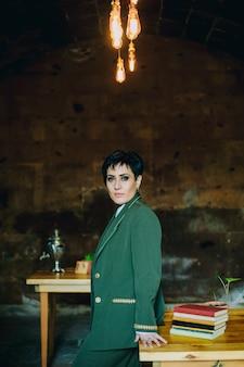 ヴィンテージのオブジェクトとレトロなカフェでカメラを注意深く見ている本と木製のテーブルに寄りかかって若い女性のミディアムショット