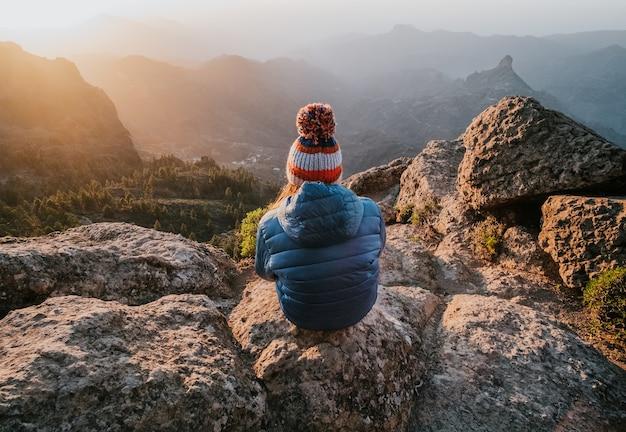 Завораживающий вид на скалистые горы с вершины и сидящую задом женщину.