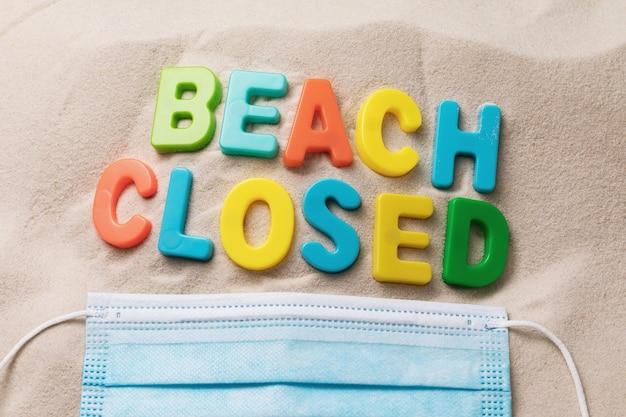 플라스틱 문자로 만든 모래 위의 메시지와 일회용 의료 마스크는 닫힌 해변을 테마로 한 개념입니다.