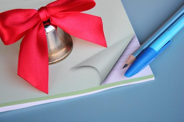Металлический колокольчик с красным бантом расположен на школьной тетради рядом с ручкой и карандашом.