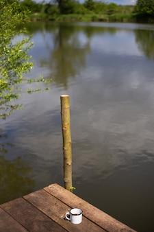 Металлическая чашка горячего кофе стоит на деревянном пирсе у озера. активный отдых на свежем воздухе, прекрасный солнечный летний день.