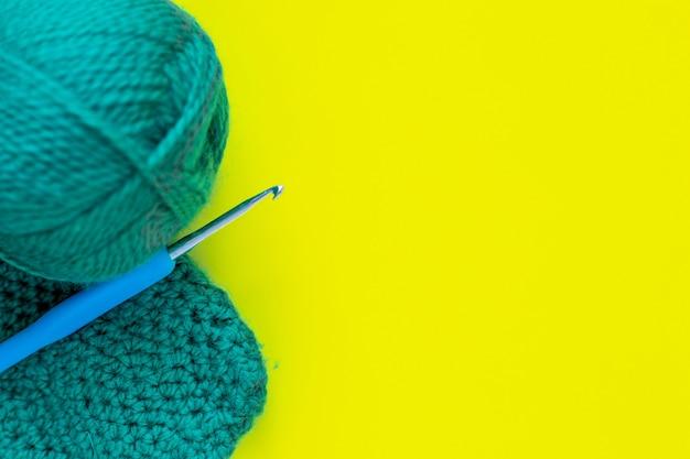 Металлический крючок с синей ручкой, моток пряжи зеленого цвета и часть связанного фрагмента лежит на с ...