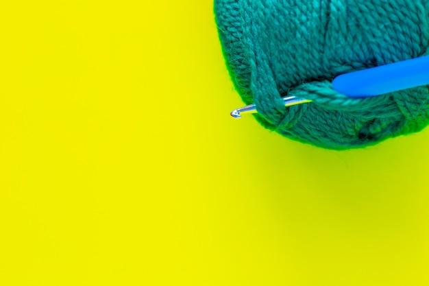 Металлический крючок с синей ручкой вставляется в моток зеленой пряжи в верхнем углу ф ...