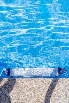 타일 바닥이있는 수영장에 난간이있는 금속 사다리