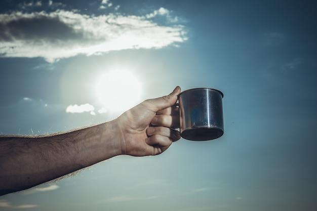 雲のある空を背景に男の手に金属製のマグカップ。碑文おはよう、国。