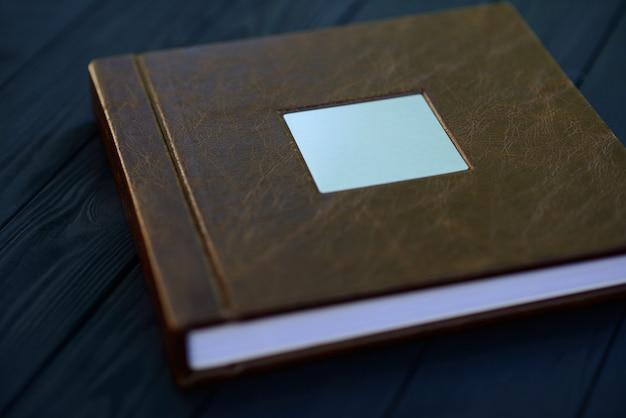 茶色の革の写真集の表紙にある金属製の銘板