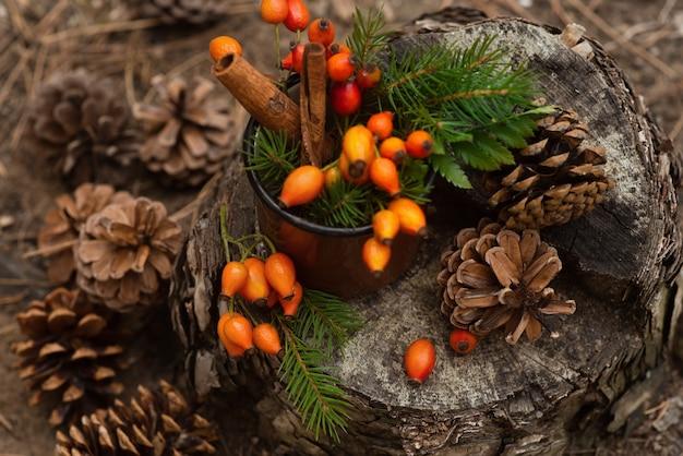 森の切り株の上に、ローズヒップ、緑の葉、トウヒの枝、円錐形の周りにある金属製の古いマグカップが立っています。新年とクリスマスの背景。冬の雰囲気。ベリー入りのヘルシーなハーブティー