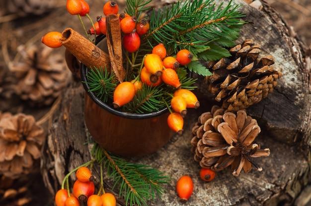 森の切り株に立っているローズヒップ、緑の葉、トウヒの枝と円錐形の金属製の古いマグカップ