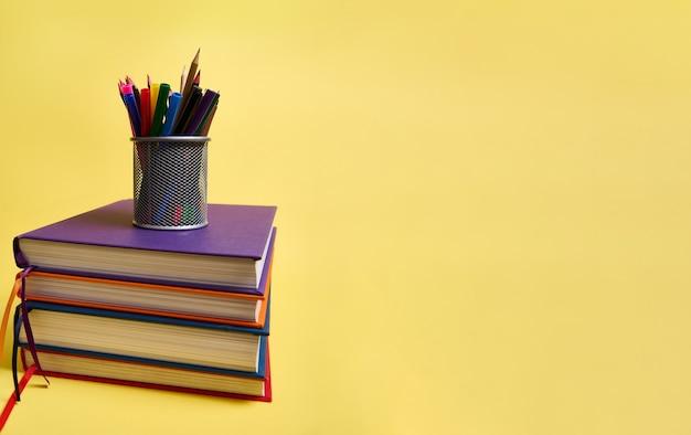 Металлическая подставка для карандашей со школьными принадлежностями на стопках разноцветных книг. концепция дня учителя, литература, знания, снова в школу, образование. изолированные на желтом фоне копией пространства