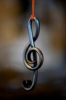 Металлический ключ для нот висит на веревке в кузнечной мастерской.