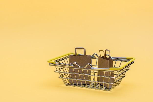 店内の金属製の買い物かごと、黄色の背景にいくつかのクラフト紙袋。ブラックフライデーギフトの販売。コピースペース