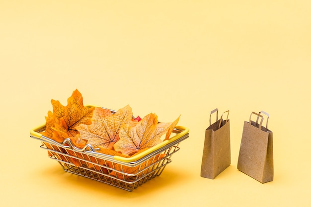 黄色い背景に紅葉とクラフト紙袋でいっぱいの店の金属製の買い物かご。ブラックフライデーギフトの販売。コピースペース
