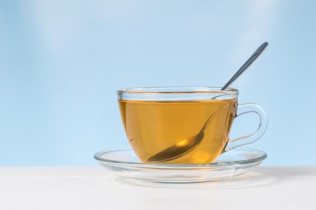 Металлическая ложка в стакане чая на белом столе. бодрящий напиток, полезный для здоровья.