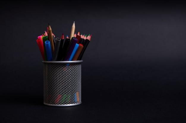 Металлическая подставка для ручек и карандашей на рабочем столе на черном фоне с местом для текста. крупный план металлического ведра с канцелярскими принадлежностями. держатель с цветными школьными принадлежностями