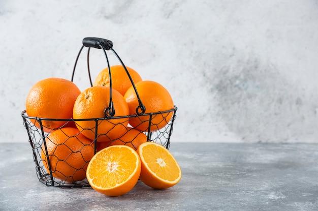 石のテーブルにジューシーなオレンジ色のフルーツがいっぱい入ったメタリックブラックバスケット。