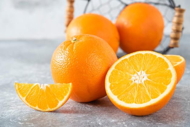 돌 테이블에 수 분이 많은 오렌지 과일의 전체 금속 검은 바구니.