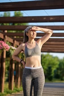 Женщина средних лет в спортивной одежде, закрывая глаза от солнца и глядя в сторону