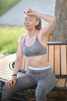 Женщина средних лет в спортивной одежде отдыхает после тренировки и выглядит уставшей