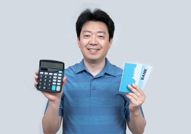 Азиатский мужчина средних лет держит в руке банковскую книжку и калькулятор