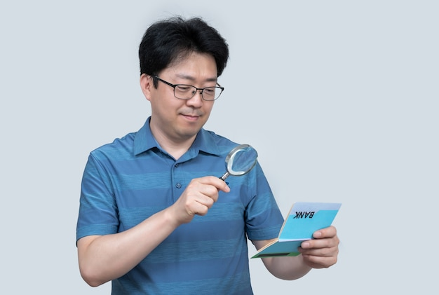 Азиатский мужчина средних лет держит банковскую книжку в руке