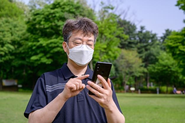 Азиатский мужчина средних лет в маске использует смартфон на лужайке.