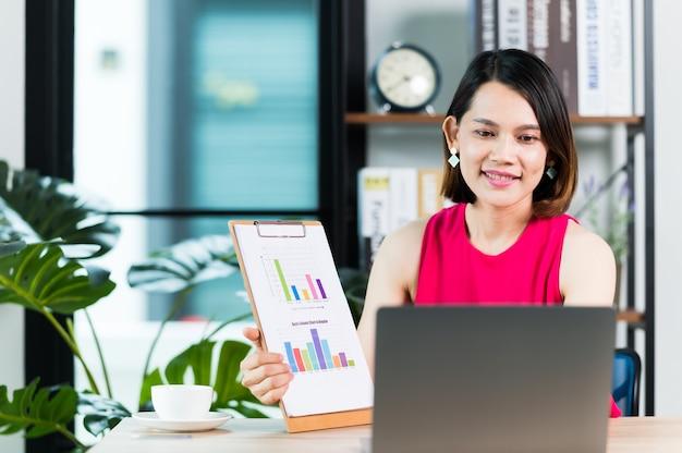 Азиатская женщина средних лет, взрослый учитель или репетитор, преподает онлайн-бизнес на ноутбуке дома. новый нормальный образ жизни во время карантина из-за коронавируса.
