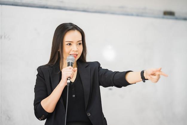 Азиатская учительница средних лет держит микрофон на доске в классе в университете