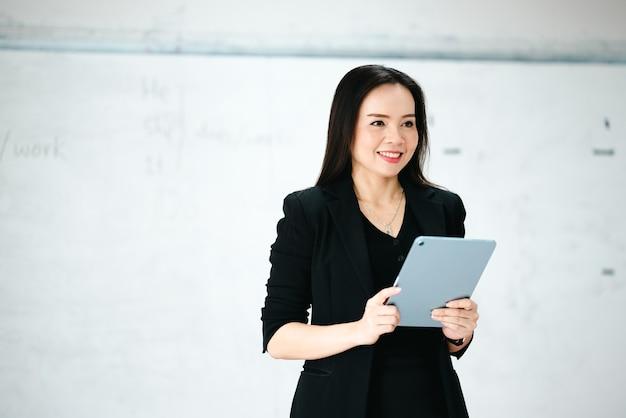 Азиатская женщина-учительница средних лет держит планшет на доске в классе в университете