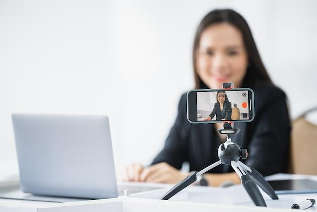 중년 아시아 여성 교사가 대학에서 노트북으로 온라인 라이브