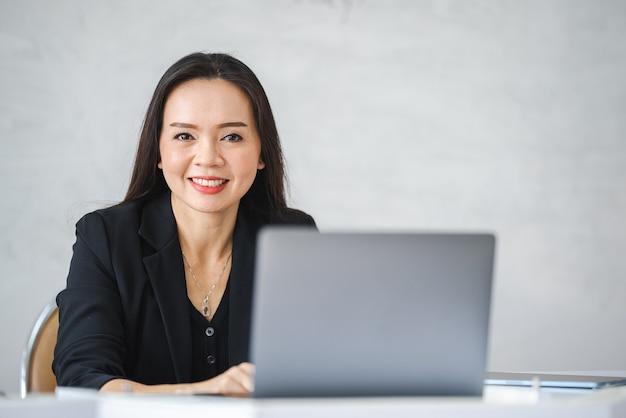 Азиатская учительница средних лет живет в университете с ноутбуком онлайн