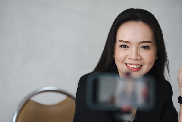 대학에서 스마트폰으로 온라인 라이브를 하는 중년 아시아 여성 교사
