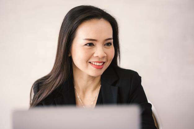 Азиатская женщина-учительница средних лет сидит в классе с ноутбуком на столе в университете