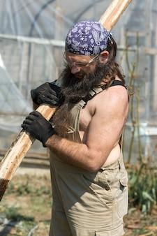Бородатый мужчина средних лет в бандане рубит бревна топором.
