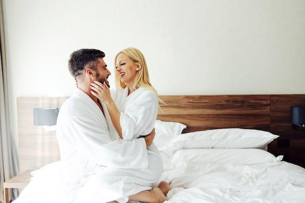 Влюбленная пара средних лет сидит на кровати в отеле, обнимается и празднует годовщину.