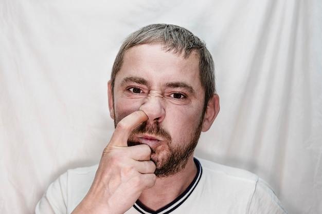 턱수염을 기른 유럽 중년 남성이 손가락으로 코를 뽑고 있다.