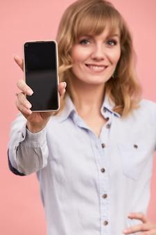 전화 화면에 쇼가 있는 중년 소녀, 금발은 분홍색 배경에 화면이 있는 전화를 들고 있습니다.