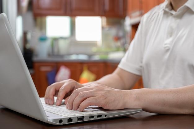 自宅で中年男性が自宅でコンピューターを使用して作業します。
