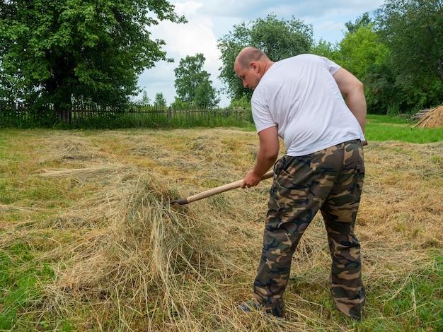 Мужчина средних лет в брюках и футболке собирает вилкой траву в штабель