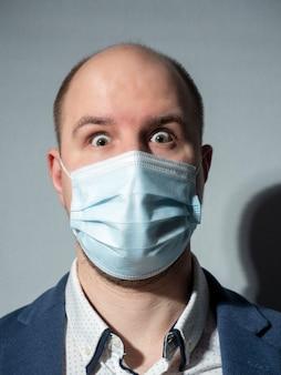 Мужчина средних лет в костюме и медицинской маске смотрит в камеру. расширенные глаза от удивления или испуга.