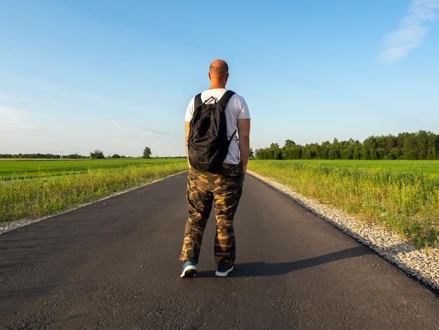 中年の男性が背中に黒いバックパックを背負ってアスファルト道路に立っています。背面図。旅行とレクリエーションの概念、未来への願望