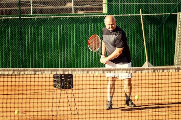 중년 남자가 코트에서 테니스를 치다. 활동과 움직임.