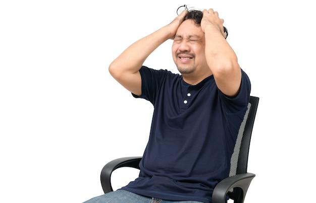 Мужчина средних лет, одетый в футболку и сидящий на стуле, был потрясен, сбит с толку и почувствовал себя неуютно на белом фоне. концепция эмоций