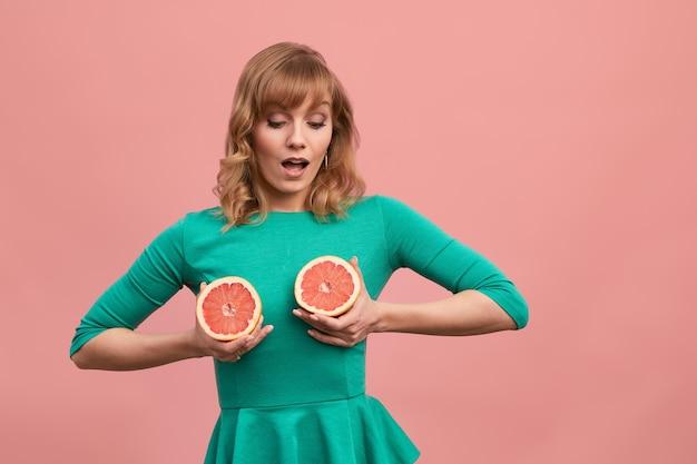 中年の女性が胸にグレープフルーツを持ち、緑のドレスを着た金髪の女性がグレープフルーツを手に持っています。健康的なダイエット食品、減量の概念。