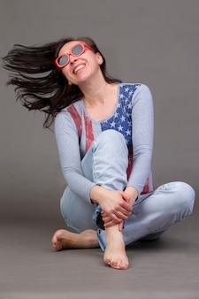 Женщина средних лет в футболке с принтом американского флага, джинсах сидит на серой стене и смеется.