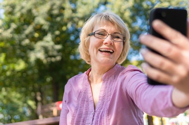 전화 통화를 하고 셀카를 찍는 중년 여성. 한 여성이 소통하고, 블로깅하고, 이메일을 확인하고 있습니다. 소셜 미디어, 네트워크.