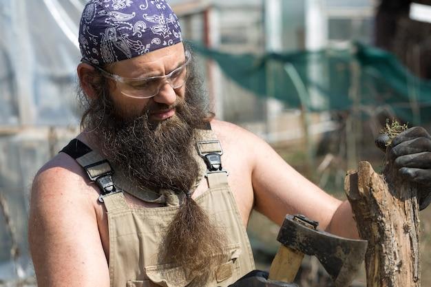 Бородатый мужчина средних лет в бандане рубит бревна топором брутальный в комбинезоне делает тяжелую работу
