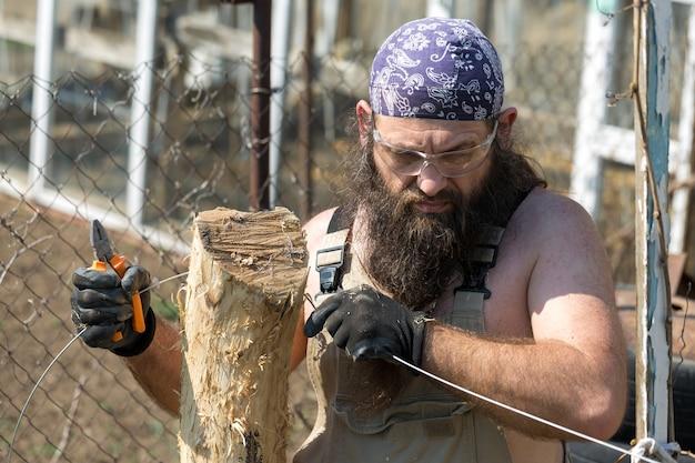 Бородатый мужчина средних лет в бандане рубит бревна топором